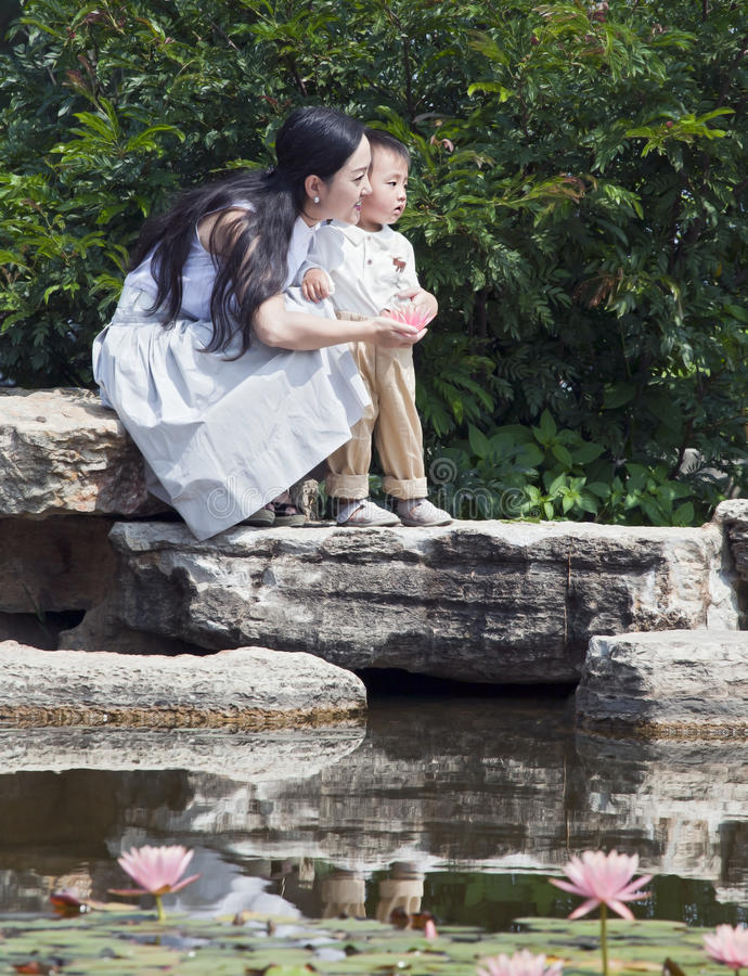 Mother And Child By Lotus Pond Stock Image