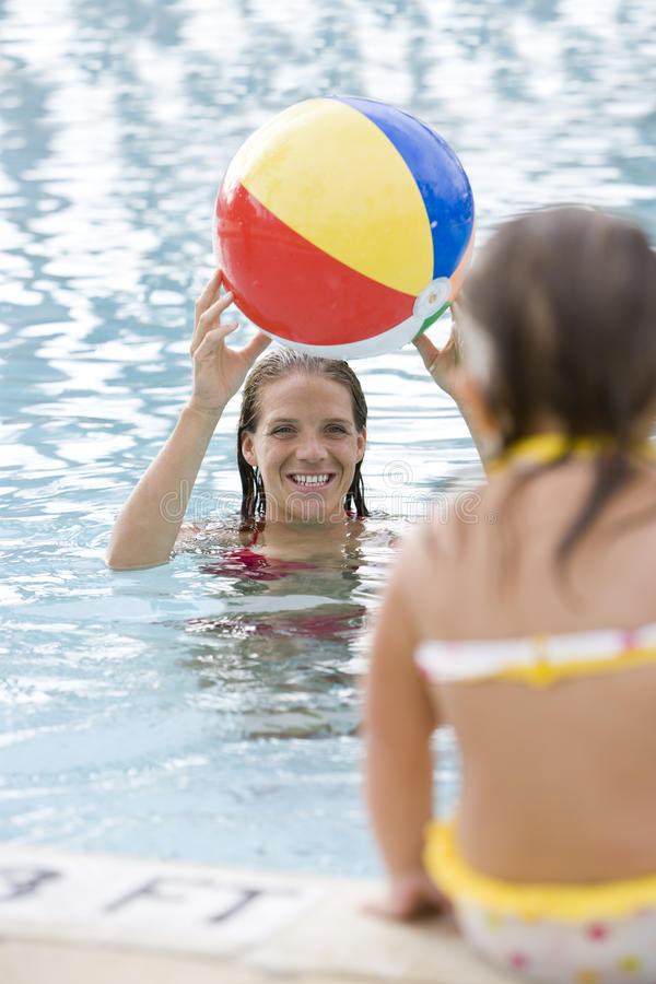 Mother and child playing with beach ball in pool royalty free stock photography