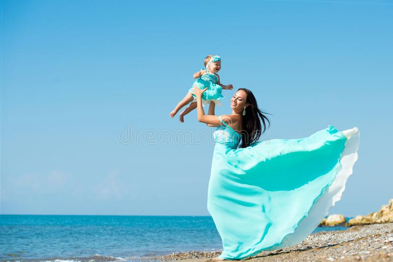 Mother and child playing on the beach. Mom throws up the baby. stock photo
