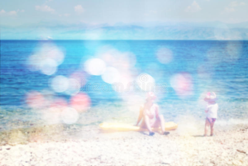 Mother and child playing on beach, summer vacation, blur abstract background with bokeh lights royalty free stock photo