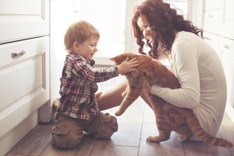 Mother and child playing with cat. Mother with her baby playing with pet on the floor at the kitchen at home