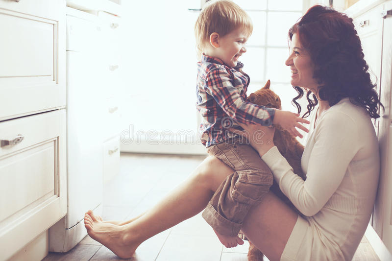 Mother and child playing with cat stock photography