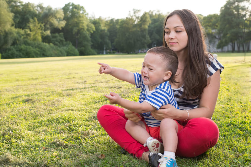 Mother and child playing at the grass. naughty boy crying and and point by his finger stock photography