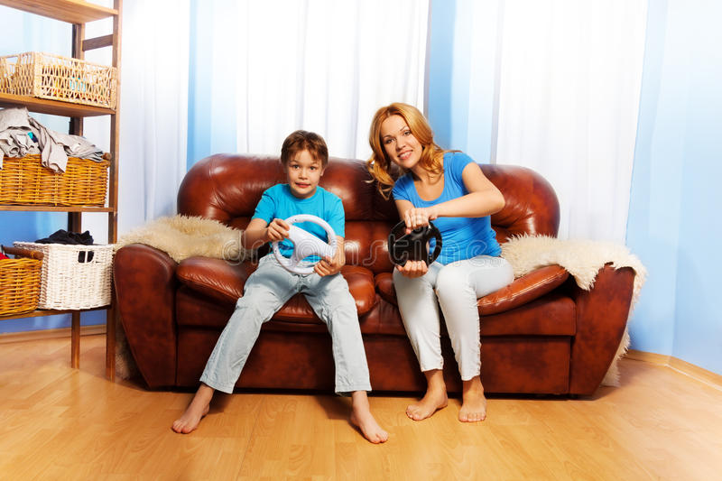 Mother and child playing with steering wheels stock photo