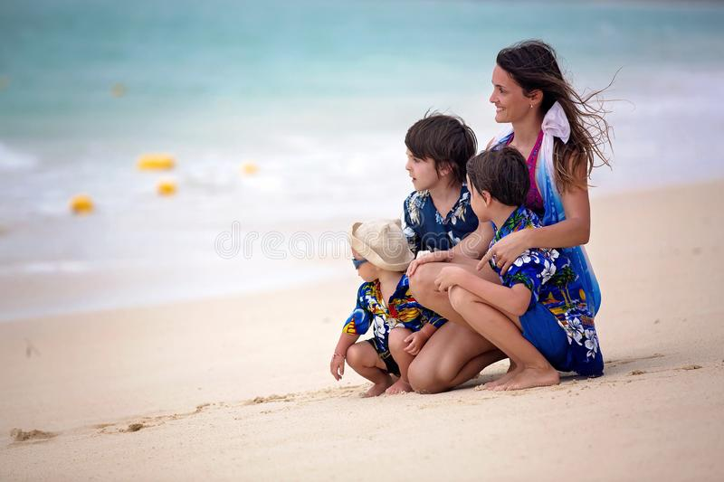 Mother and child playing at tropical beach. Family sea summer vacation. Mom and kid, toddler boy, play in the water. Ocean and. Water fun for parent and kids stock image