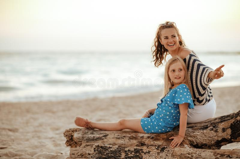 Mother and child pointing at something while sitting on beach royalty free stock photography