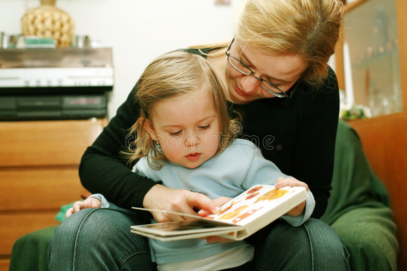 Mother and child reading. Mother and child read a book together at home