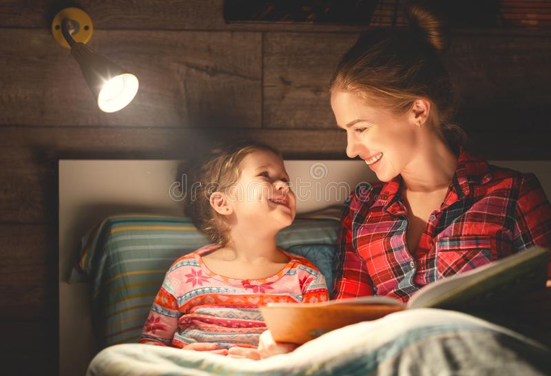 Mother and child reading book in bed before going to sleep stock photography