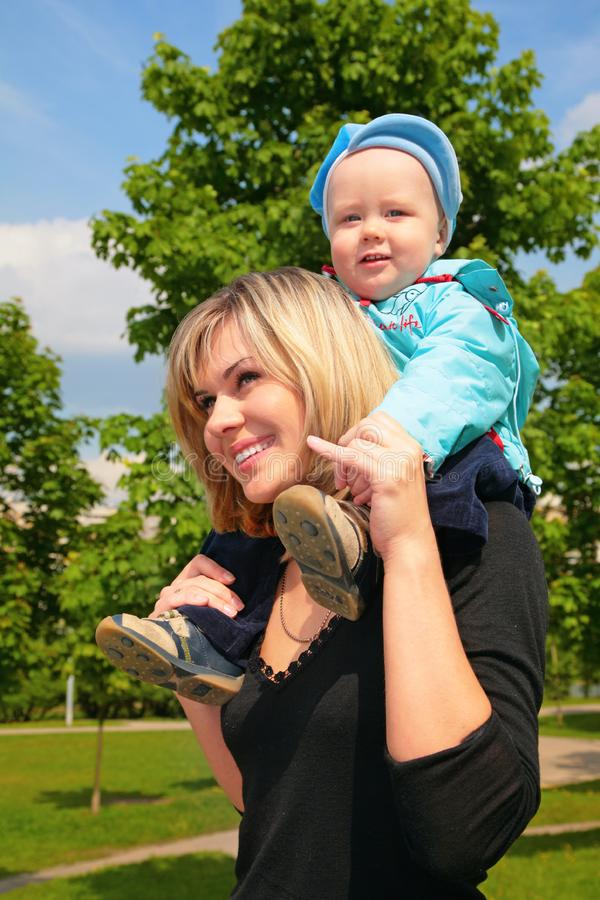 Mother with child on shoulders outdoor stock photos