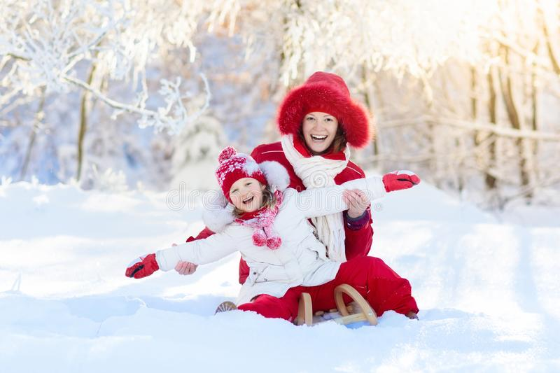 Mother and child sledding. Winter snow fun. Family on sleigh. Mother and baby on sleigh ride. Child and mom sledding. Toddler kid riding sledge. Children play royalty free stock image