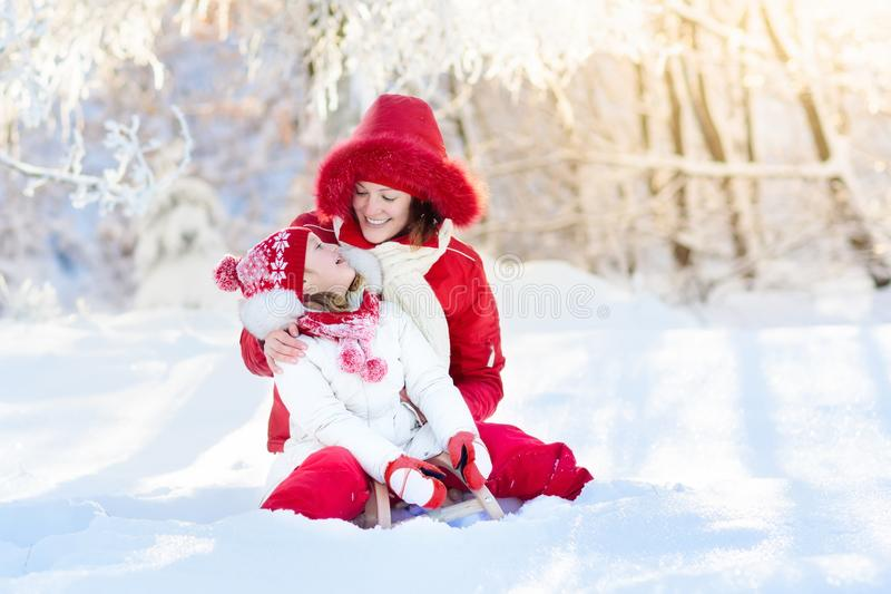 Mother and child sledding. Winter snow fun. Family on sleigh. Mother and baby on sleigh ride. Child and mom sledding. Toddler kid riding sledge. Children play royalty free stock photos