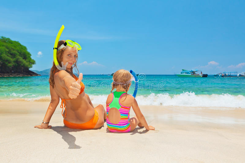 Mother with child snorkeling on summer beach holiday. Happy family - mother with baby girl have fun in beach pool with sea surf. Travel healthy lifestyle, people stock photography