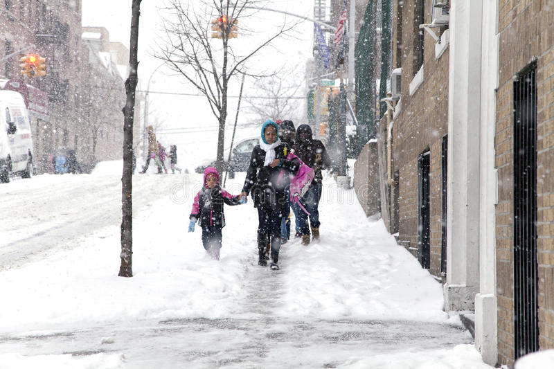 Mother and child during snow storm in New York. BRONX, NEW YORK - JANUARY 21: A small child and mother weathering a 6 to 10 inch snow storm and teen temperatures royalty free stock image