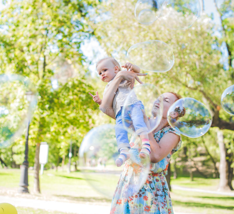 Mother and child in soap blowers. The are happy and joy. boy smiling and laughing. Summer day in park. royalty free stock photo