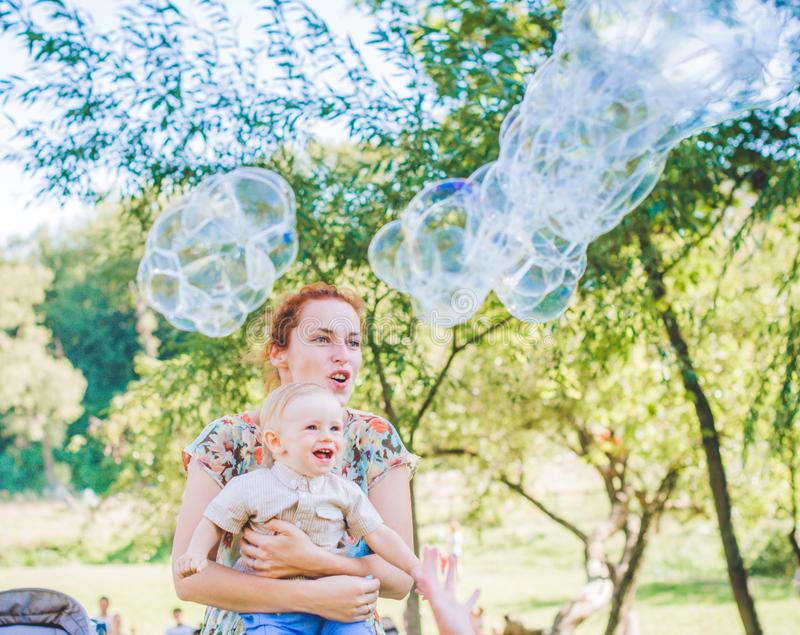 Mother and child in soap blowers. The are happy and joy. boy smiling and laughing. Summer day in park. stock photo