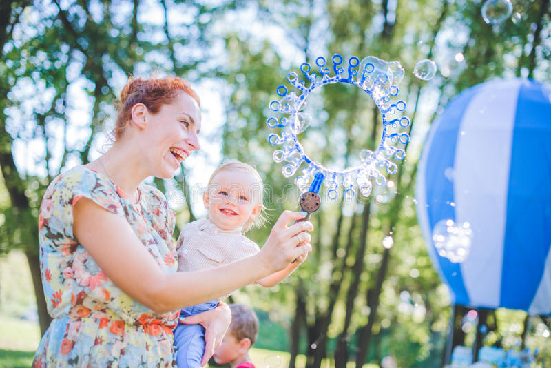 Mother and child in soap blowers. The are happy and joy. boy smiling and laughing. Summer day in park. royalty free stock images