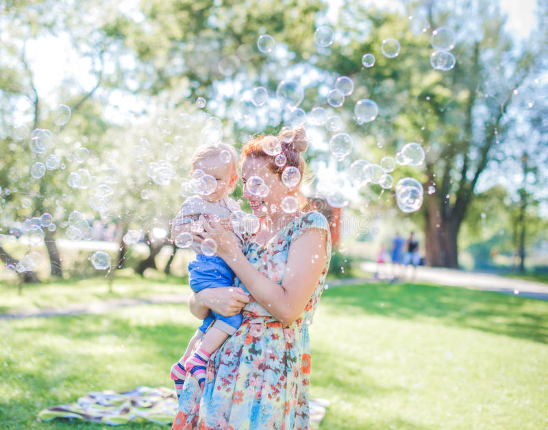 Mother and child in soap blowers. The are happy and joy. boy smiling and laughing. Summer day in park. stock image