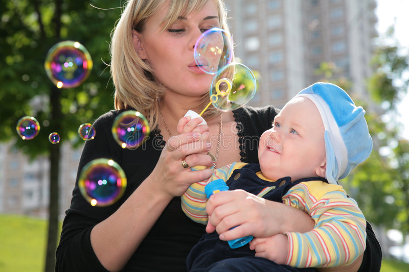 Mother with child is started up with soap bubbles