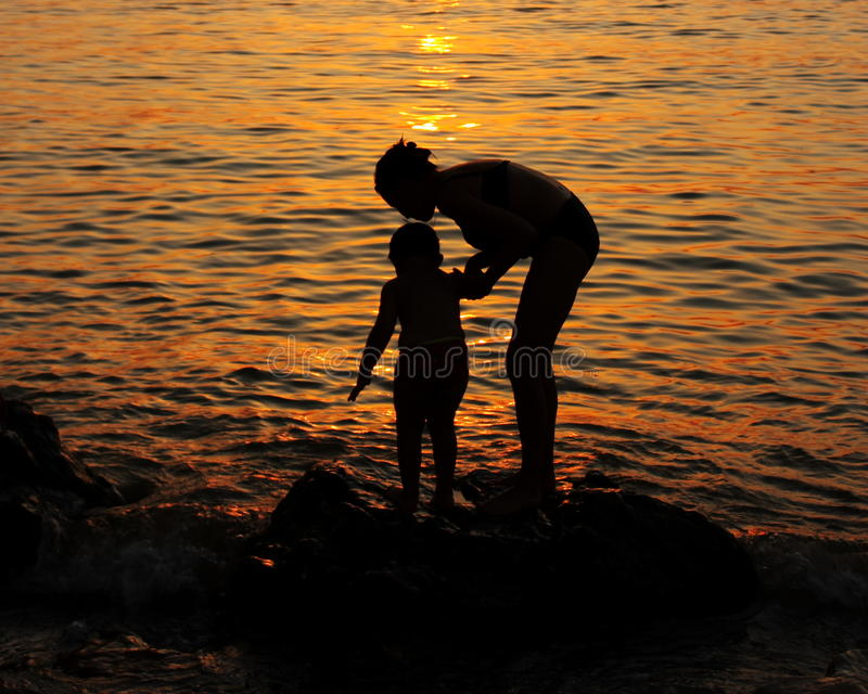 Mother and Child : Sunset Wallpaper - Stock Picture. Mother and Child : Sunset Wallpaper - Silhouettes against sun light on evening sea background royalty free stock photos