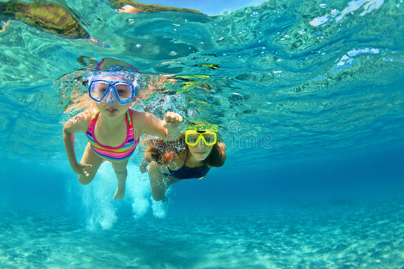 Mother with child swim underwater with fun in sea. Happy family - mother with baby girl dive underwater with fun in sea pool. Healthy lifestyle, active parent royalty free stock photography