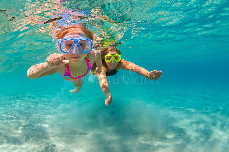 Mother with child swim underwater with fun in sea. Happy family - mother with baby girl dive underwater with fun in sea pool. Healthy lifestyle, active parent stock image