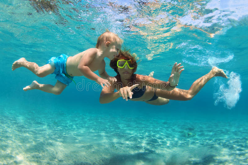 Mother with child swim underwater with fun in sea. Happy family - mother with baby son dive underwater with fun in sea pool. Healthy lifestyle, active parent royalty free stock images