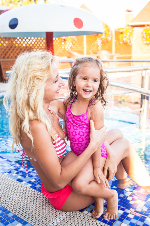 Mother and child at the swimming pool. Mother is teaching her daughter to swim at the swimming pool royalty free stock images