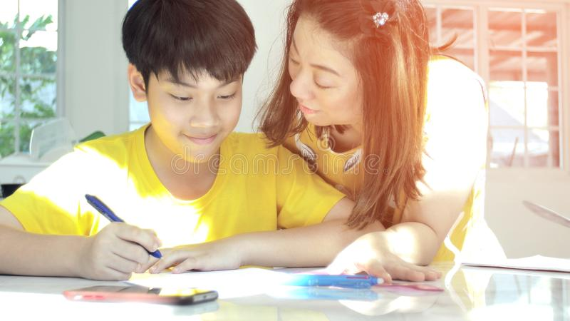 Mother and child teachings and doing your homework. Portrait of asian mother and child teachings and doing your homework together at home stock images