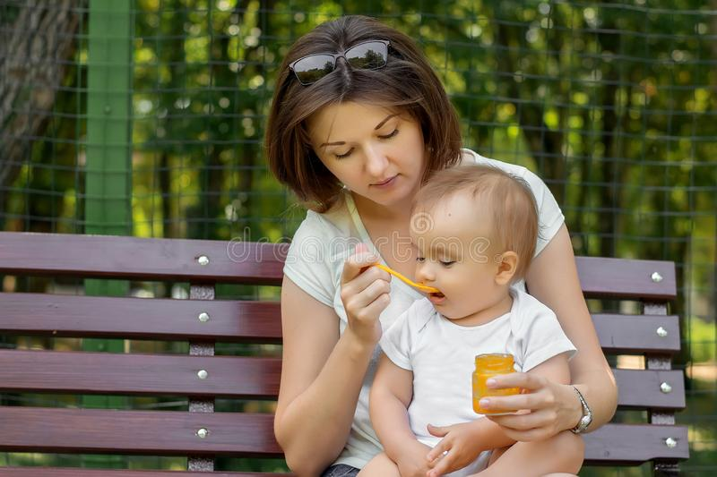 Mother and child together: young mom feeding her little baby child with vegetable puree on spoon in park. Happy motherhood royalty free stock images