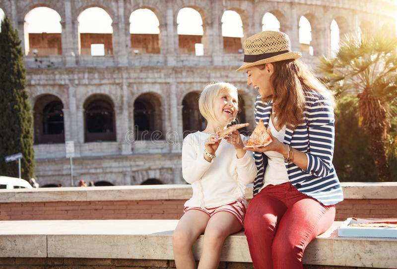 Mother and child travellers in front of Colosseum eating pizza stock images
