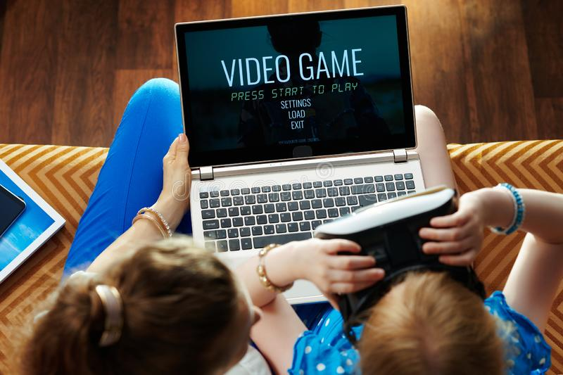 Mother and child in VR glasses and playing video games. Modern mother and child sitting on divan in the modern living room in VR glasses and playing video games stock images