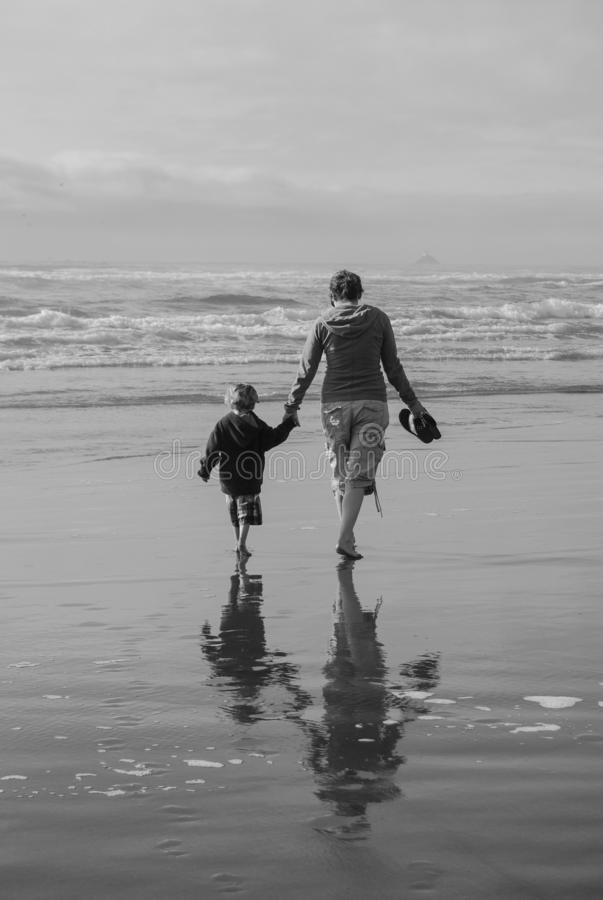 BW Vertical Mother Child Silhouette on Beach. Mother and child walking hand in hand on deserted beach. Private time with parent and child. Bonding with barefoot stock images
