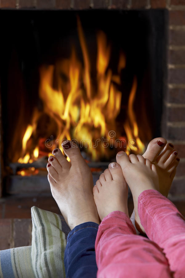 Mother And Child Warming Bare Feet By Fire stock photos