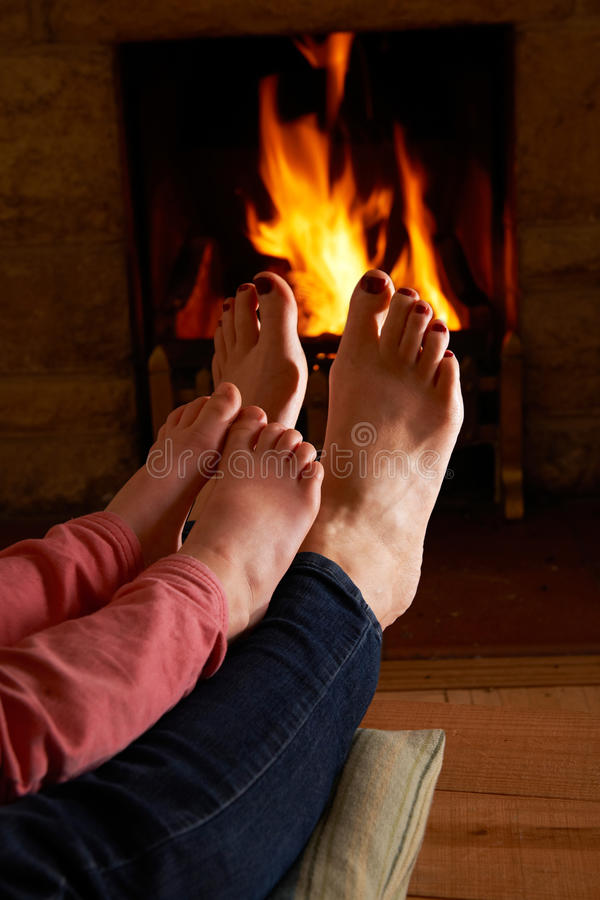 Mother And Child Warming Feet By Fire royalty free stock image