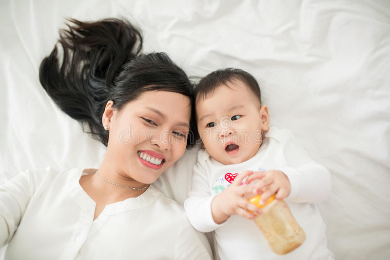 Mother and child on a white bed. Mom and baby girl playing. Parent and little kid relaxing at home. Family having fun together. Be stock photo