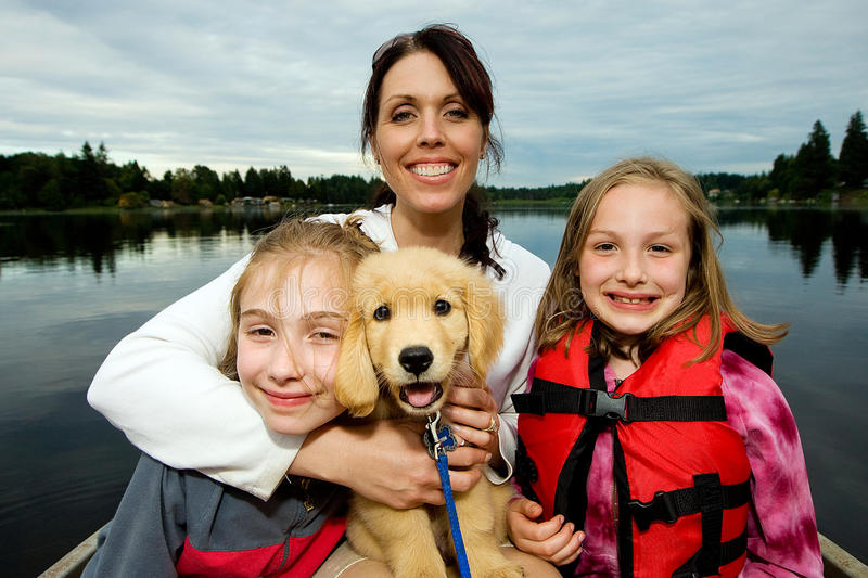 Mother and children on a boat. A pretty Mom with her two girls on a boat with a golden retriever puppy royalty free stock photos