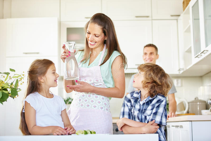 Mother and children with carafe water. In the kitchen royalty free stock images