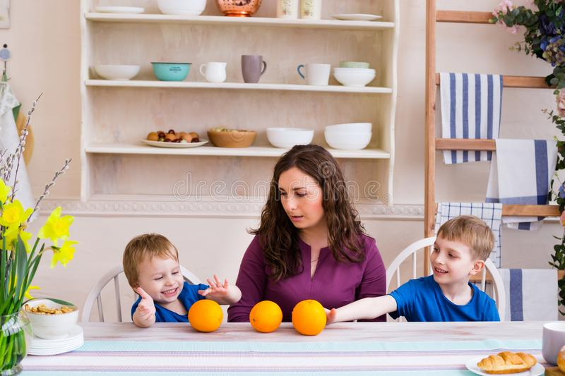 Mother and kids at the table in the kitchen. Happy family concept stock image