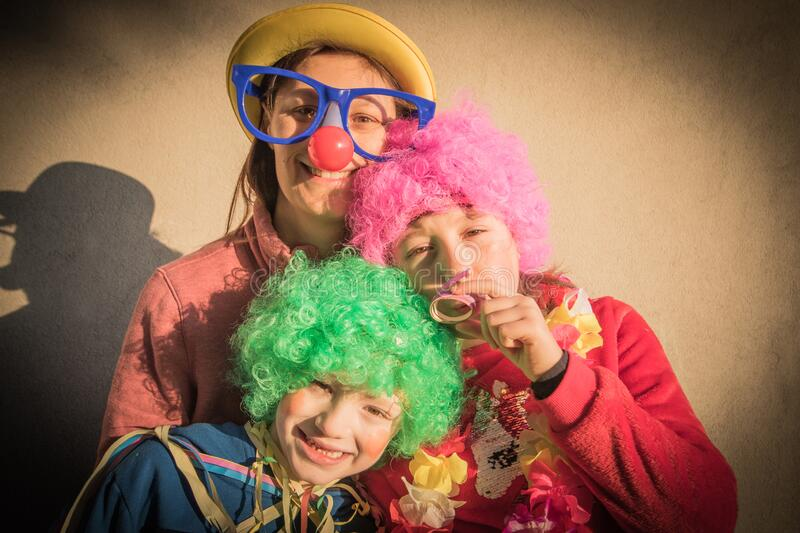 Mother and children in carnival mask smiling togheter outdoor royalty free stock image