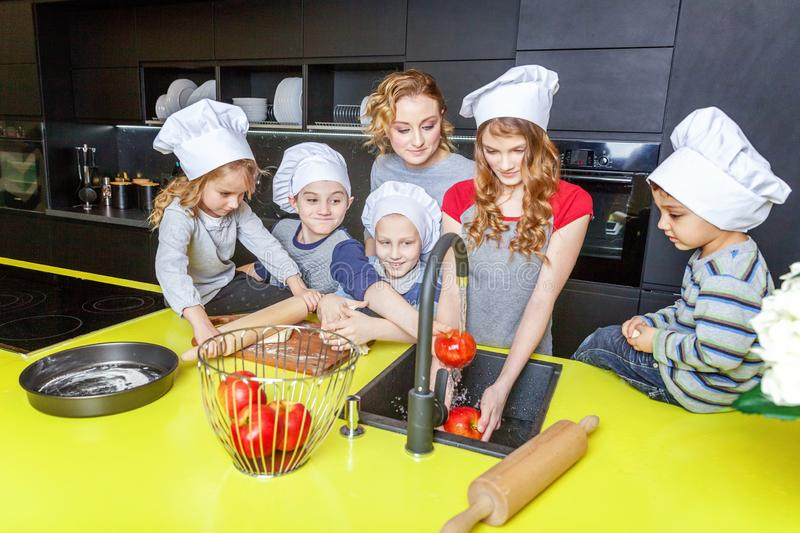 Mother and children cooking in kitchen and having fun. Happy family in kitchen. Mother and five children preparing dough, bake apple pie. Mom, daughters and sons stock images