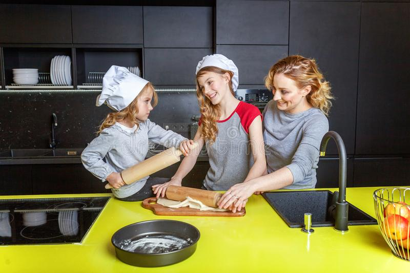 Mother and children cooking in kitchen and having fun. Happy family in kitchen. Mother and two children preparing dough, bake apple pie. Mom and daughters royalty free stock images