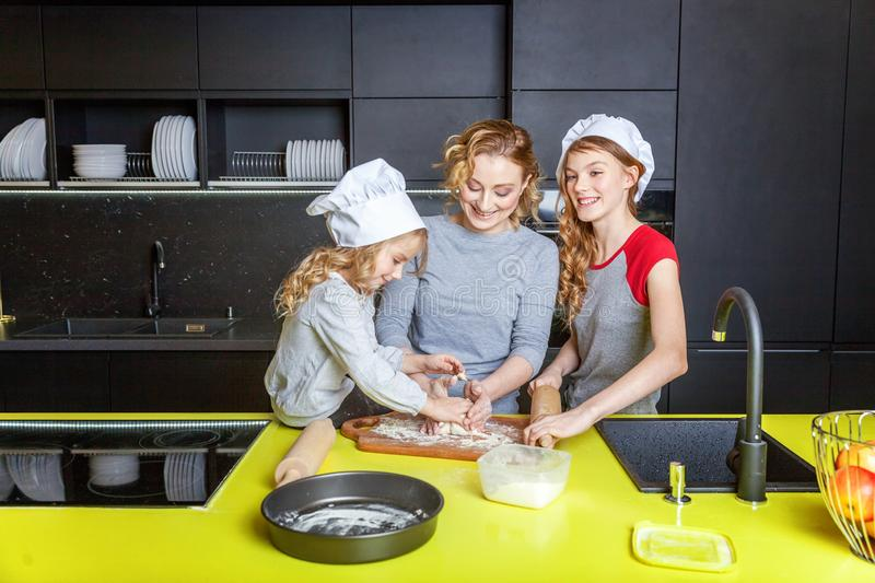 Mother and children cooking in kitchen and having fun. Happy family in kitchen. Mother and two children preparing dough, bake apple pie. Mom and daughters royalty free stock photography