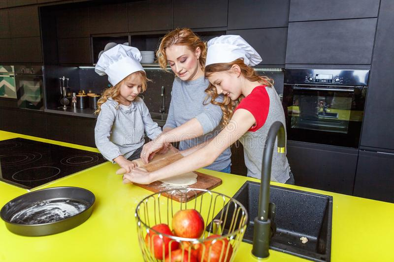 Mother and children cooking in kitchen and having fun. Happy family in kitchen. Mother and two children preparing dough, bake apple pie. Mom and daughters stock image
