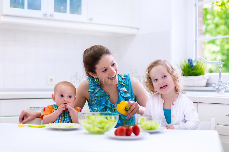 Mother and children cooking in a white kitchen royalty free stock photos