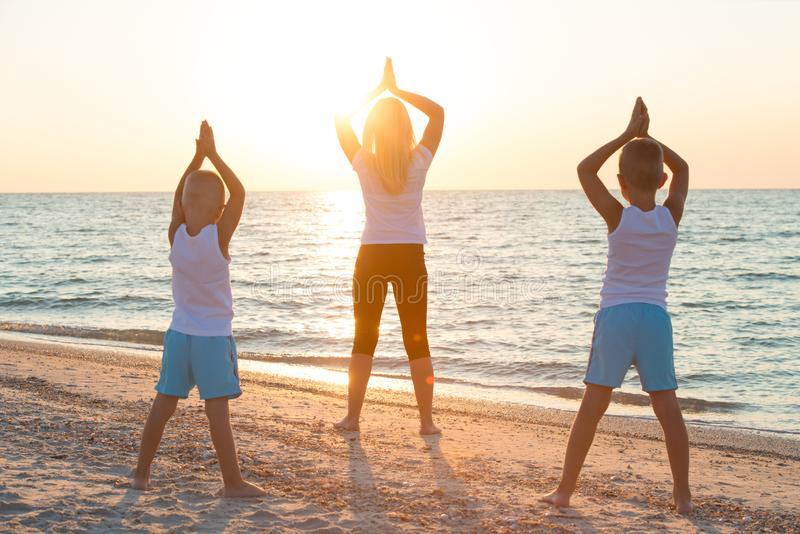Mother and children do exercises on the beach, they meet the sunrise.Fitness, sport, yoga and healthy lifestyle concept. royalty free stock image