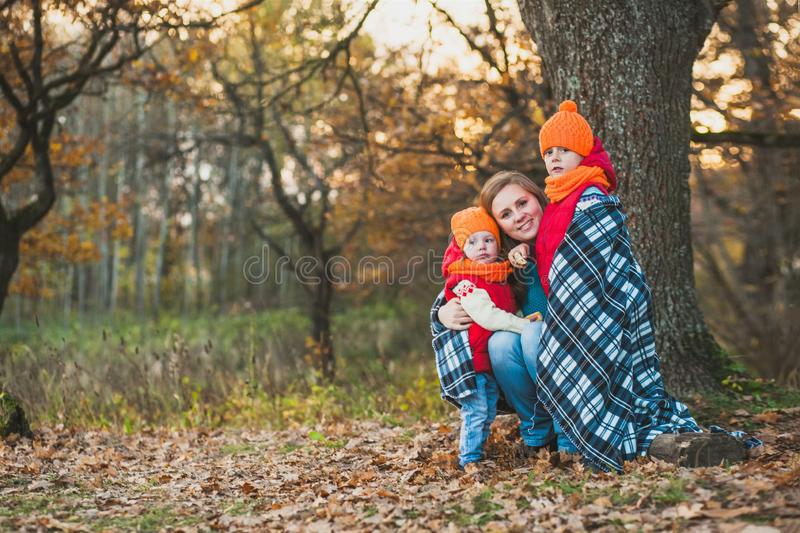 Mother with children dressed in bright orange hats, wrapped in a blanket for a walk in the autumn park royalty free stock images