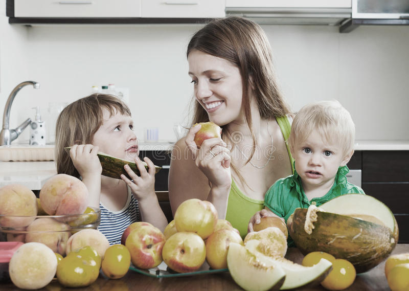 Mother with children eating melon. Ordinary mother with children eating melon and other fruits over table at home interior royalty free stock image
