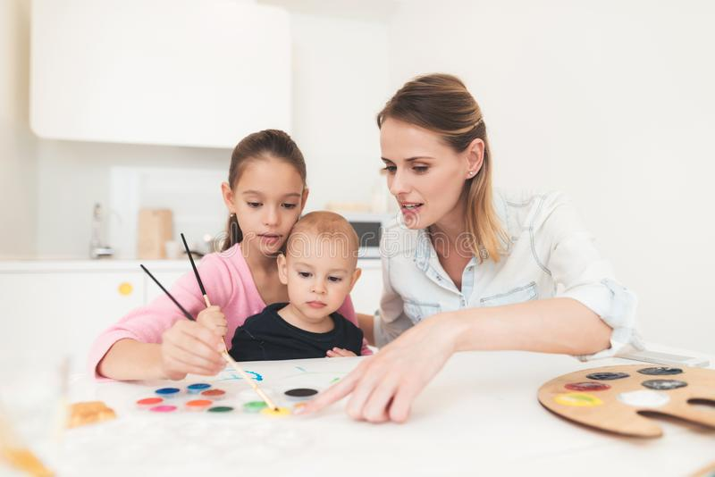 Mother and children are engaged in drawing. They have fun in the kitchen. The girl is holding her younger brother in her royalty free stock photography