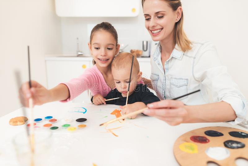 Mother and children are engaged in drawing. They have fun in the kitchen. The girl is holding her younger brother in her stock photography
