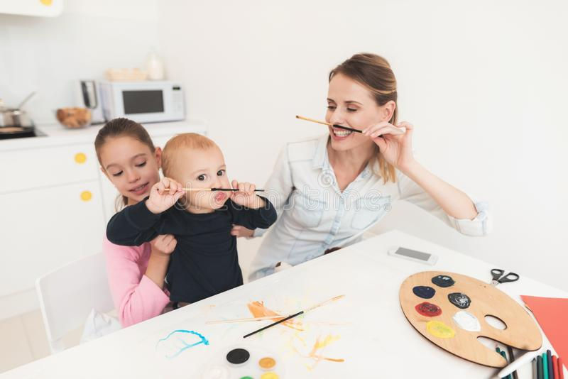 Mother and children are engaged in drawing. They have fun in the kitchen. The girl is holding her younger brother in her stock image